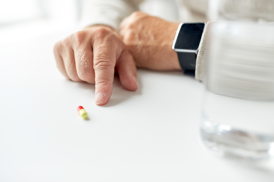 elderly patient wearing a smart watch pointing to medication inside a senior living facility