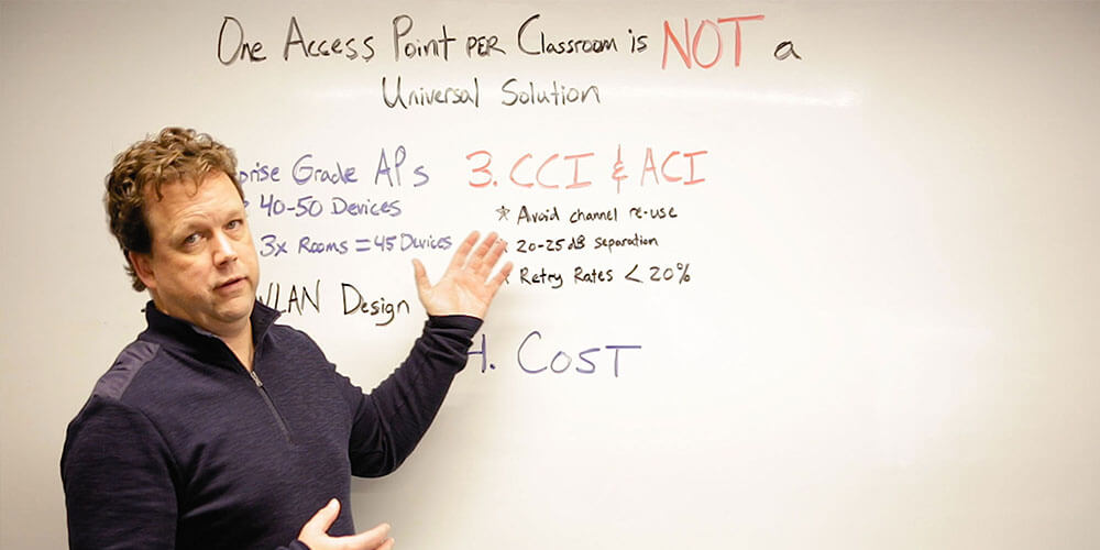 Network engineer Michael McNamee teaching a whiteboard lesson about one access point per classroom