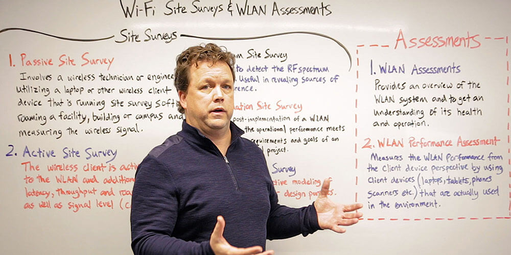 Network engineer Michael McNamee teaching a whiteboard lesson about wifi site surveys